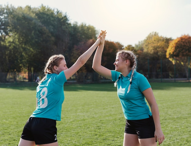 Giocatori di calcio felici alti cinque