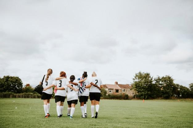 Giocatori di calcio femminile rannicchiati e camminare insieme