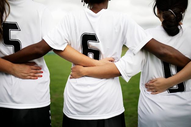 Giocatori di calcio femminile rannicchiati e in piedi insieme