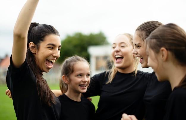Giocatori di football femminile allegri che celebrano la loro vittoria