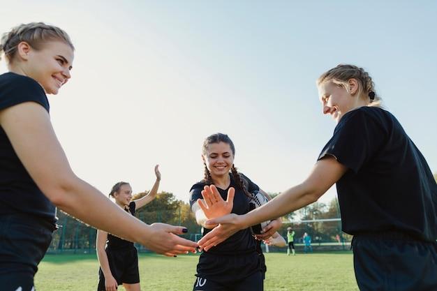 Giocatori di rugby femminile che uniscono le mani