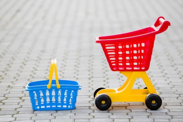 Giocattoli colorati di plastica luminosi, carrello e cestino all'aperto
