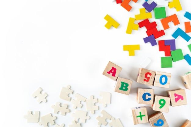 Giocattoli colorati per bambini su sfondo bianco. inquadra dallo sviluppo di blocchi di legno, automobili e puzzle.