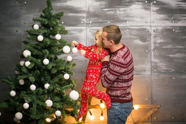 Giocattoli d'attaccatura della figlia e del padre su un albero di natale