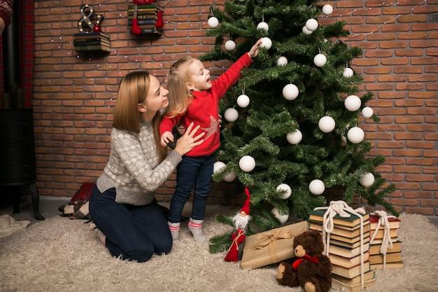 Giocattoli d'attaccatura della figlia e della madre su un albero di natale
