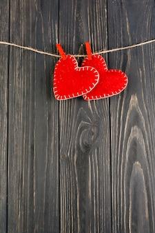 Giocattoli di feltro a forma di cuore rosso che pendono sulla corda