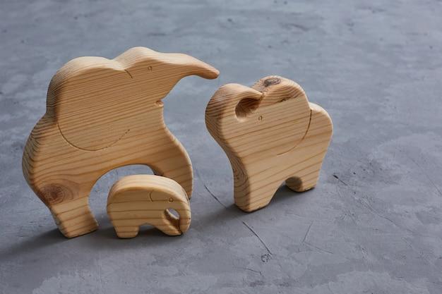 Giocattoli di legno. una famiglia di 3 elefanti scolpiti in un puzzle su un tavolo di cemento grigio