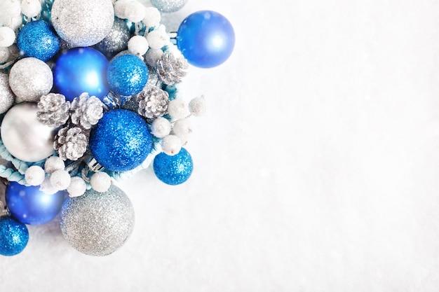 Giocattoli di natale blu e argento su sfondo chiaro.