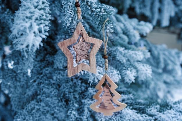 Giocattoli di natale in legno su un bellissimo abete innevato in inverno