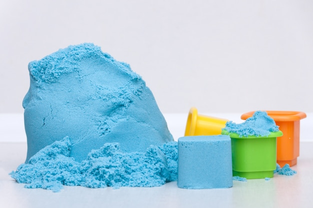 Giocattoli di plastica di istruzione dei bambini e sabbia cinetica sui precedenti bianchi. copia spazio
