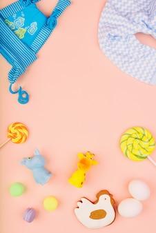 Giocattoli e vestiti per bambini sono disposti su uno sfondo rosa delicato. pan di zenzero festivo a forma di pollo, due uova bianche e caramelle. concetto di infanzia.