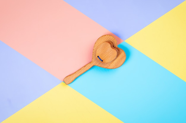 Giocattoli in legno ecologici, sonagli a forma di cuore su sfondo isolato rosa, blu e giallo.