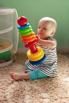 Giocattoli logici educativi per bambini. un bambino raccoglie una piramide colorata. giochi montessori per lo sviluppo del bambino. sviluppo iniziale