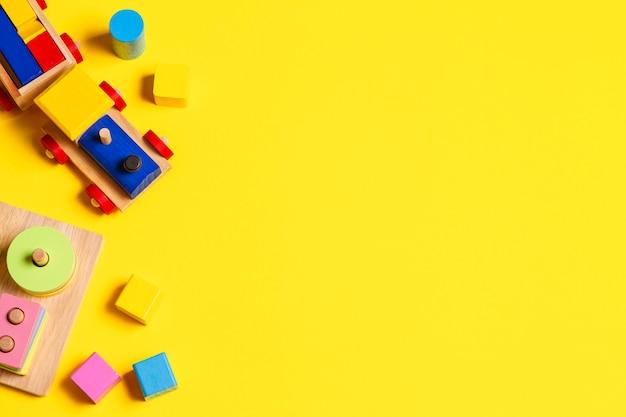 Giocattoli per bambini in legno per bambini su sfondo giallo