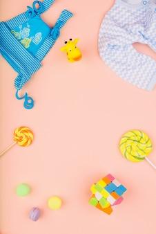 Giocattoli per bambini, rubino cubo, vestiti e caramelle dolci sono disposti su uno sfondo rosa delicato. concetto di infanzia.