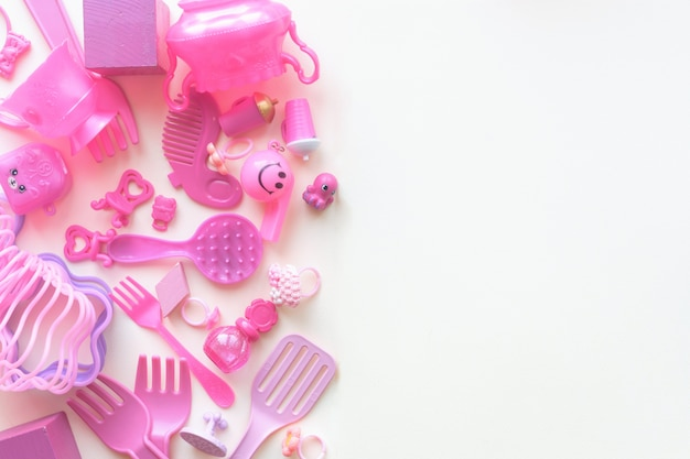 Giocattoli rosa baby su fondo bianco. vista dall'alto. bambino disteso. copyspace