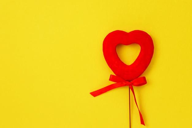 Giocattolo a forma di cornice e cuore sulla superficie gialla