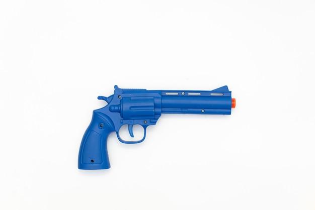 Giocattolo blu della pistola fatto di plastica isolato su fondo bianco