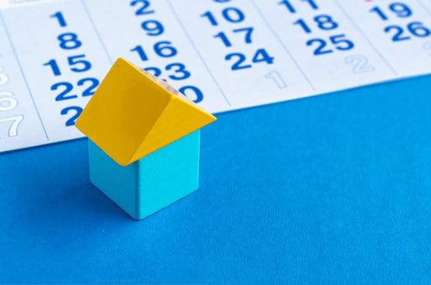Giocattolo cubo di legno come simbolo di casa e calendario sul blu