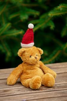 Giocattolo del piccolo orsacchiotto e cappello di natale sulla tavola di legno con i rami attillati su fondo