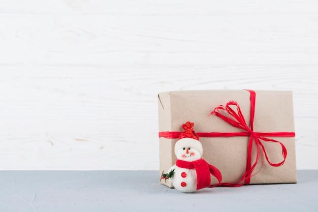 Giocattolo del pupazzo di neve con regalo di natale avvolto