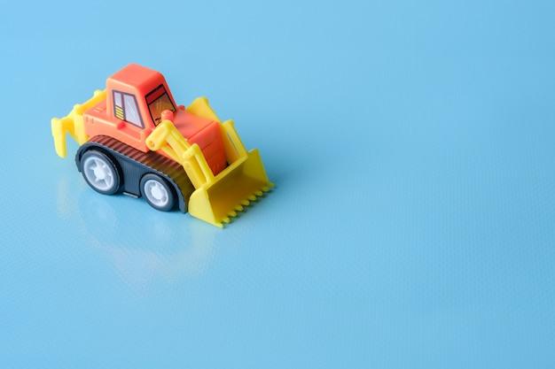 Giocattolo del trattore sullo spazio blu della copia e del fondo
