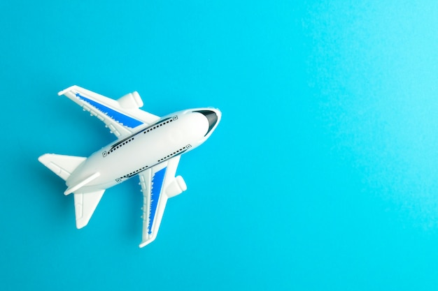 Giocattolo dell'aereo bianco del primo piano sull'azzurro. concetto di viaggiare