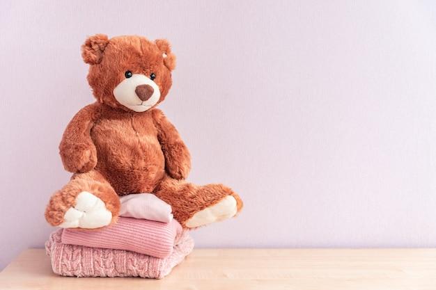 Giocattolo dell'orsacchiotto e pila di abbigliamento femminile lavorato a maglia