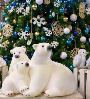 Giocattolo di orsi polari figurina, vicino all'albero di natale. decorazioni natalizie, decorazioni per alberi di natale.