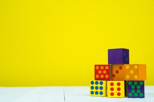 Giocattolo di puzzle del blocchetto quadrato sulla tavola con fondo giallo