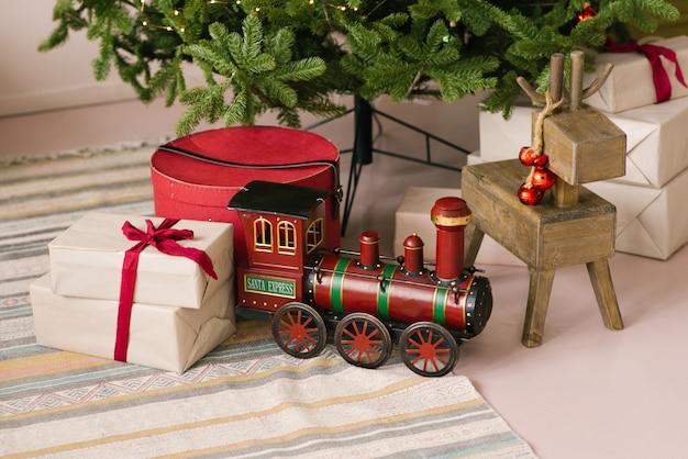 Giocattolo di santa claus christmas express e vecchi giocattoli e regali di legno dei cervi sotto l'albero di natale