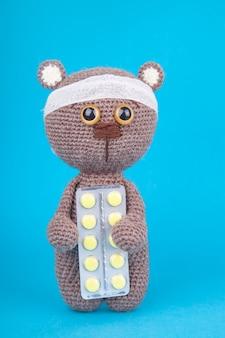 Giocattolo fai da te. cucciolo di orso bruno lavorato a maglia con compresse. prevenzione delle malattie infantili. .