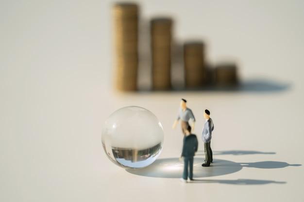 Giocattolo miniatura di affari con il vetro del globo su superficie bianca
