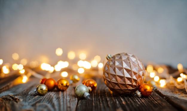 Giocattolo palla albero di natale giaceva su un tavolo di legno contro un bokeh di luci natalizie.