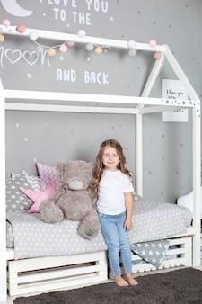 Giocattolo preferito. la bambina si siede sull'orsacchiotto dell'abbraccio del letto nella sua camera da letto. il bambino si prepara ad andare a letto. tempo piacevole in accogliente camera da letto. un bambino gioca nella stanza dei suoi bambini con un giocattolo. arredamento della camera dei bambini