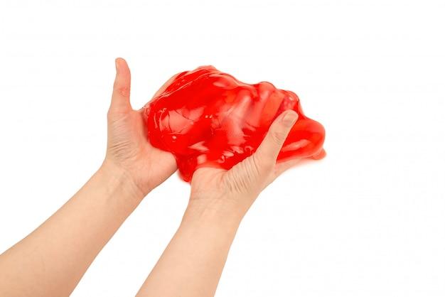 Giocattolo rosso della melma in mano della donna isolata su bianco.