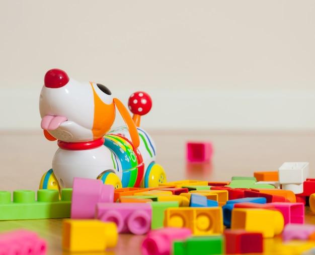 Giocattolo simpatico cane tra blocchi giocattolo di gomma