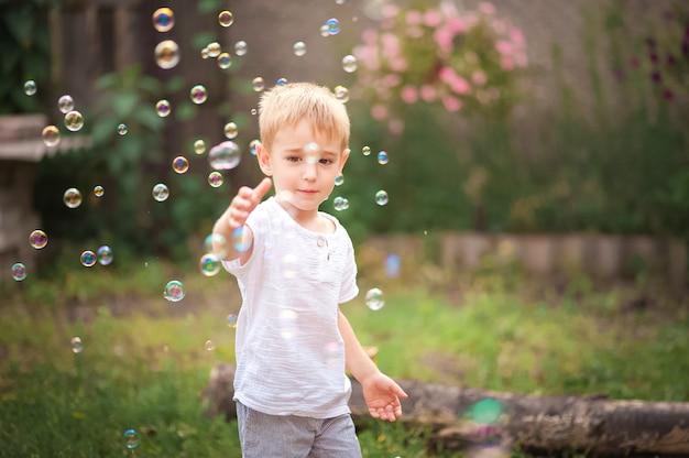 Giochi di bolle di sapone. il ragazzo nel cortile sta giocando con una pistola ad acqua.