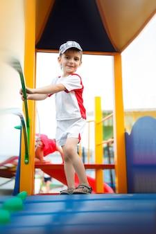 Giochi felici - bel ragazzo nel cappello nel parco giochi