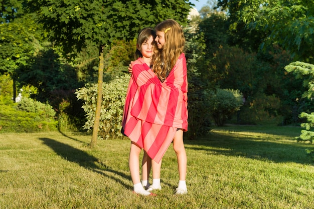 Gioco abbracciante della scolara di due amiche della bambina