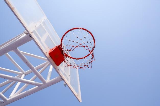 Gioco all'aperto di sport della corte di pallacanestro sul fondo del cielo blu