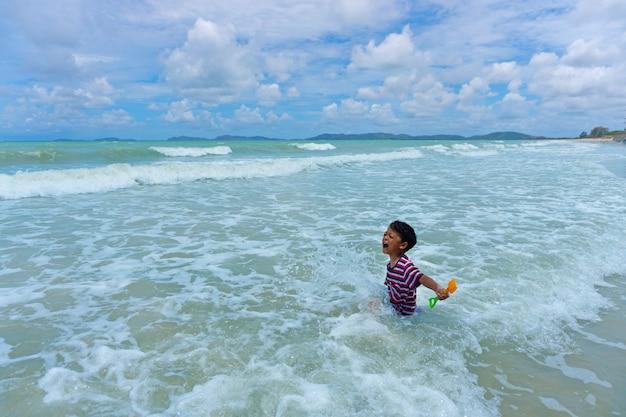 Gioco asiatico del bambino nel mare