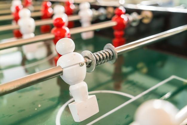 Gioco da tavolo di calcio con il giocatore rosso e bianco.