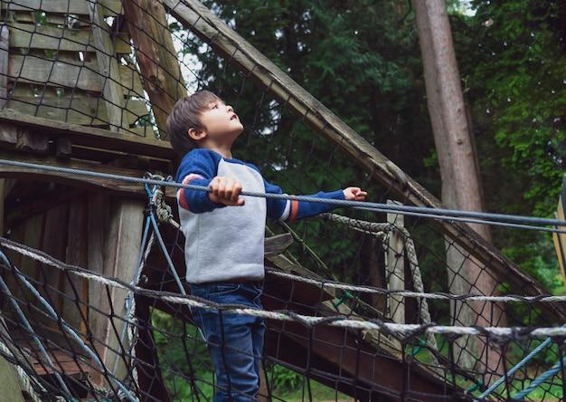 Gioco del bambino all'aperto in un parco avventura