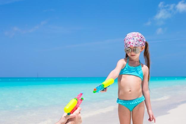Gioco della bambina con la pistola di acqua sulla spiaggia tropicale