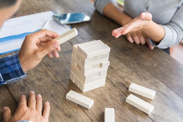 Gioco di abilità fisiche e mentali. mantenere l'equilibrio ragazza costruisce torre di blocchi di legno. attività di intrattenimento. educazione, sviluppo. le ragazze raccolgono una costrizione tentacolare di blocchi di legno