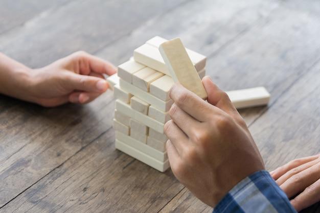 Gioco di abilità fisiche e mentali. mantenere l'equilibrio ragazza costruisce torre di blocchi di legno. attività di intrattenimento. istruzione, sviluppo. le ragazze raccolgono una costrizione tentacolare di blocchi di legno