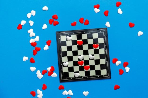 Gioco di dama con cuori rossi e bianchi su blu