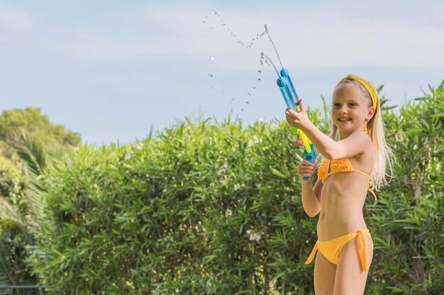 Gioco di lotta della pistola a acqua del gioco della ragazza nel giardino