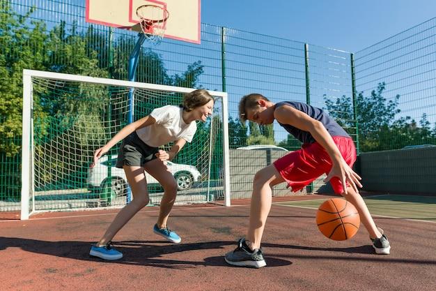 Gioco di pallacanestro streetball con due giocatori, ragazza e ragazzo adolescenti.